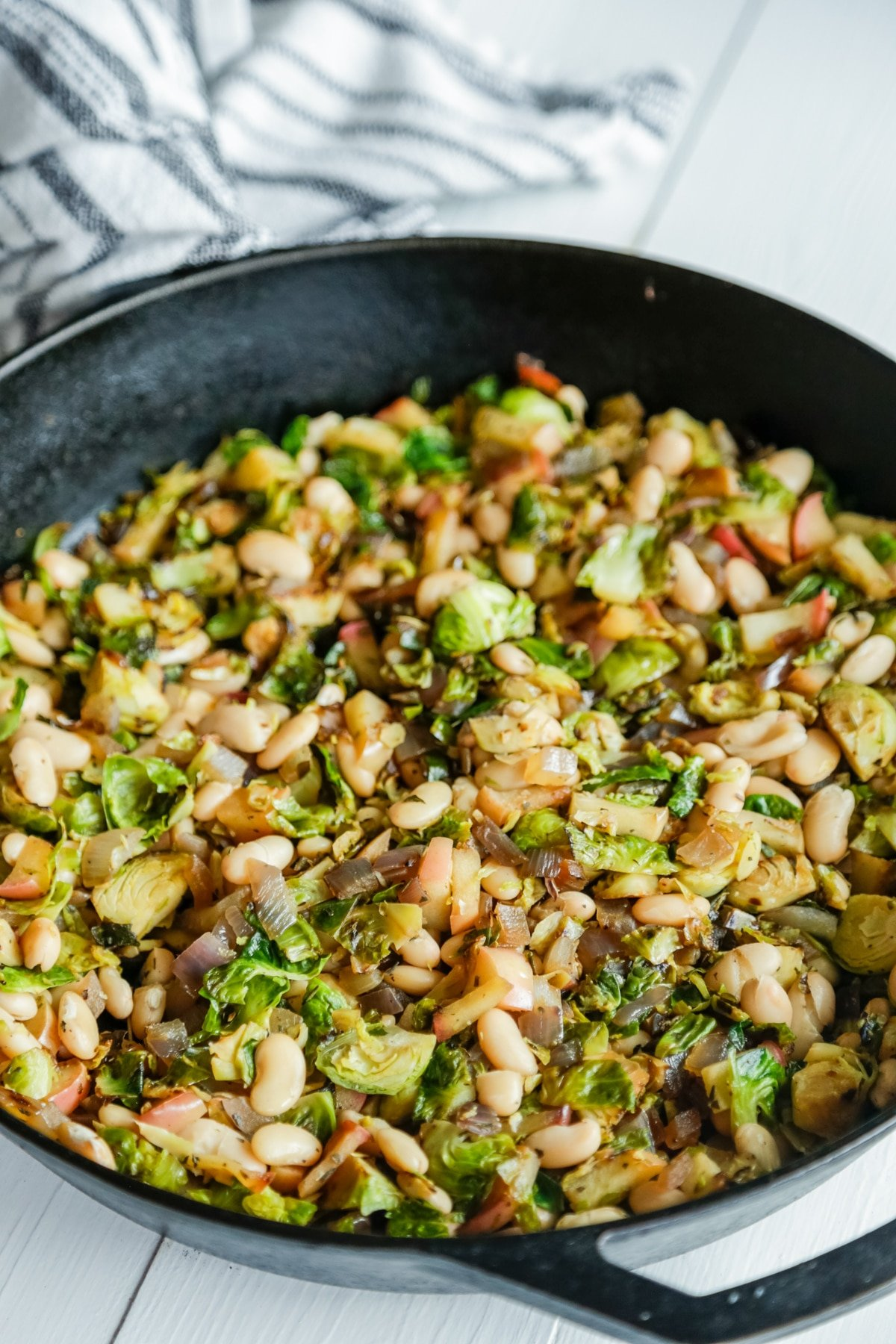 An iron skillet with Brussels sprouts, apple, and cannellini beans.