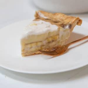 A slice of banana cream pie on a white plate.