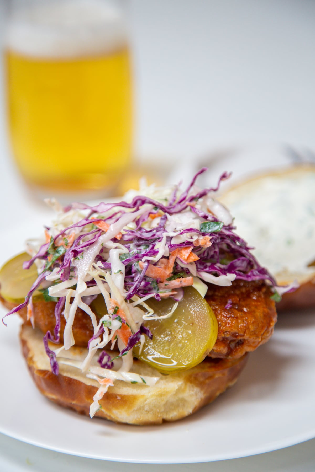 A fried chicken sandwich with pickles and creamy coleslaw on top of it and a glass of beer in the background.