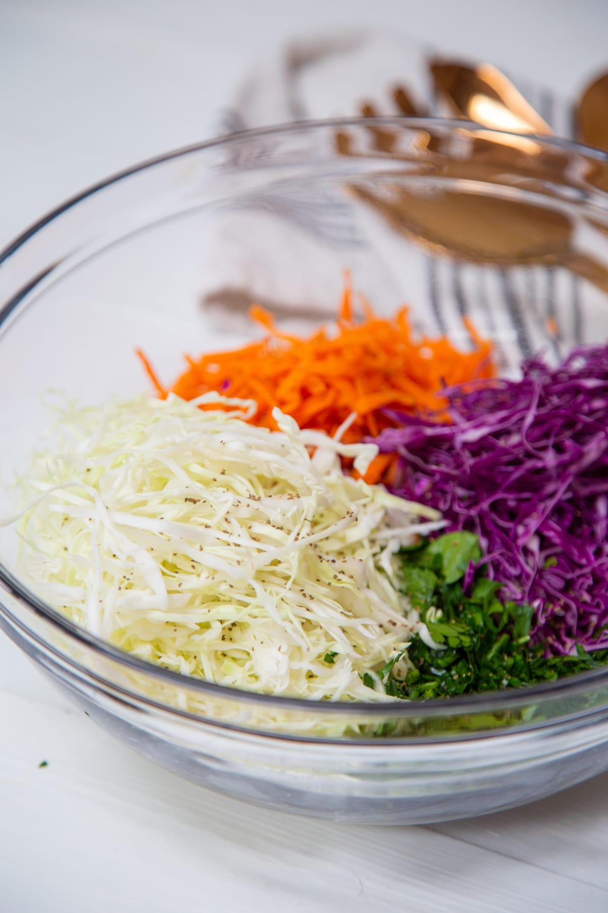 A clear glass bowl filled with shredded green and red cabbage, grated orange carrots, and chopped parsley.