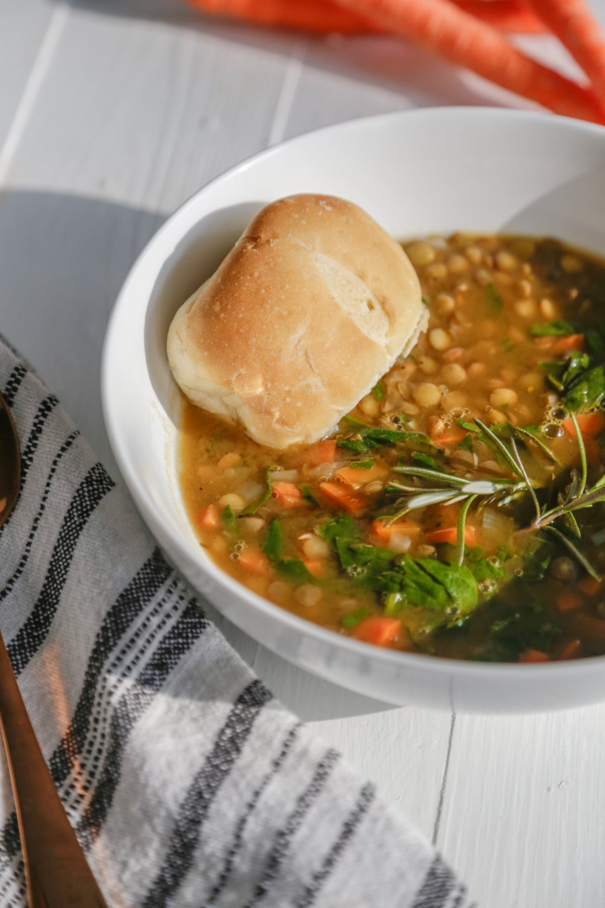 An overhead shot of lentil and carrot soup with a piece of bread in the bowl and carrots in the background.