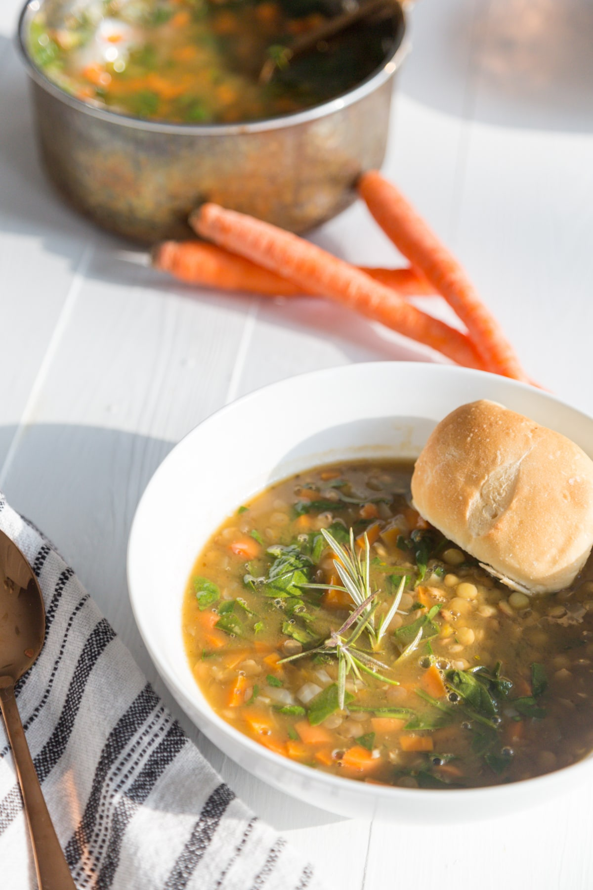 A white bowl with lentil and vegetable soup with a roll of bread in the bowl and a stack of carrots on a white table next to a copper pot of the soup.