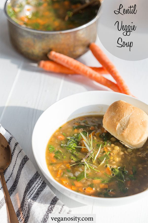 A Pinterest pin for veggie lentil soup with a picture of a white bowl of soup with a bread roll in the soup and a stack of carrots and the pot of soup in the background.