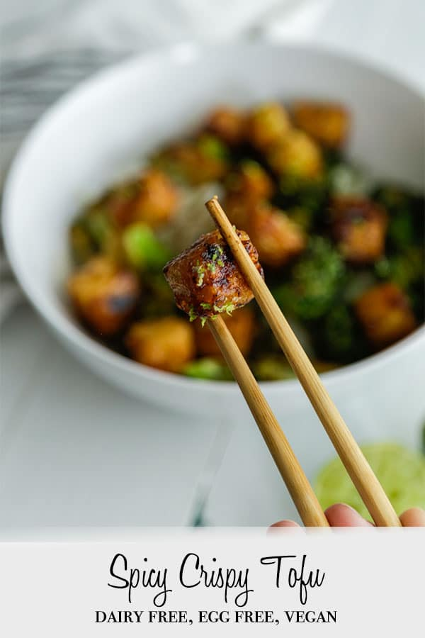 A Pinterest pin for spicy crispy tofu bites with a picture of a white bowl with crispy tofu, broccoli, rice, and a pair of chopsticks holding a cube of the tofu.