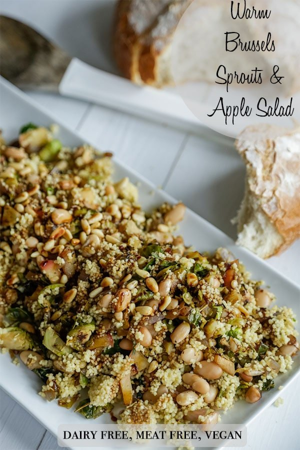 A Pinterest pin for a warm couscous, Brussels Sprouts, and apple salad with a picture of a rectangular platter with the salad.