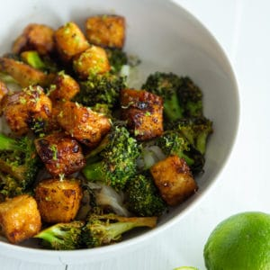 A white bowl with cubed fried tofu and broccoli over rice with a 1/2 of a lime, squeezed.