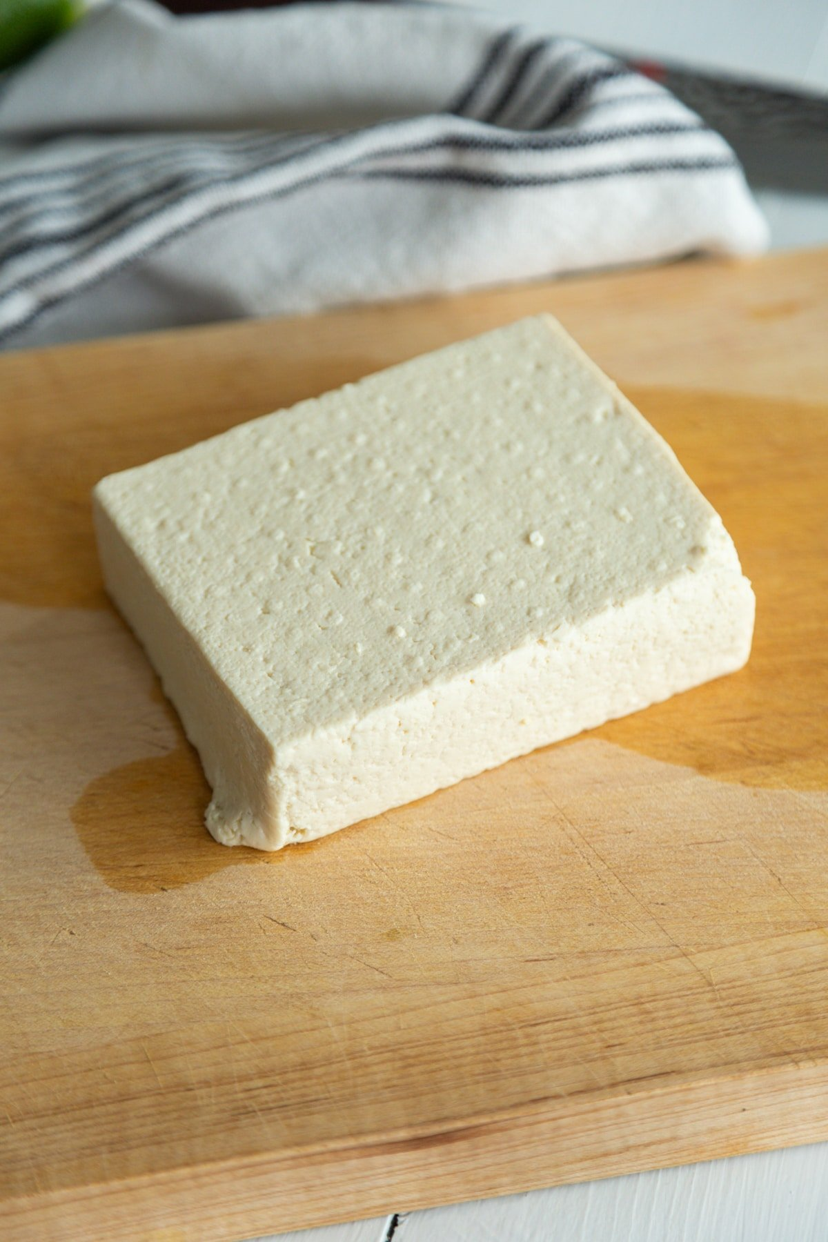 A square piece of tofu on a wooden board.
