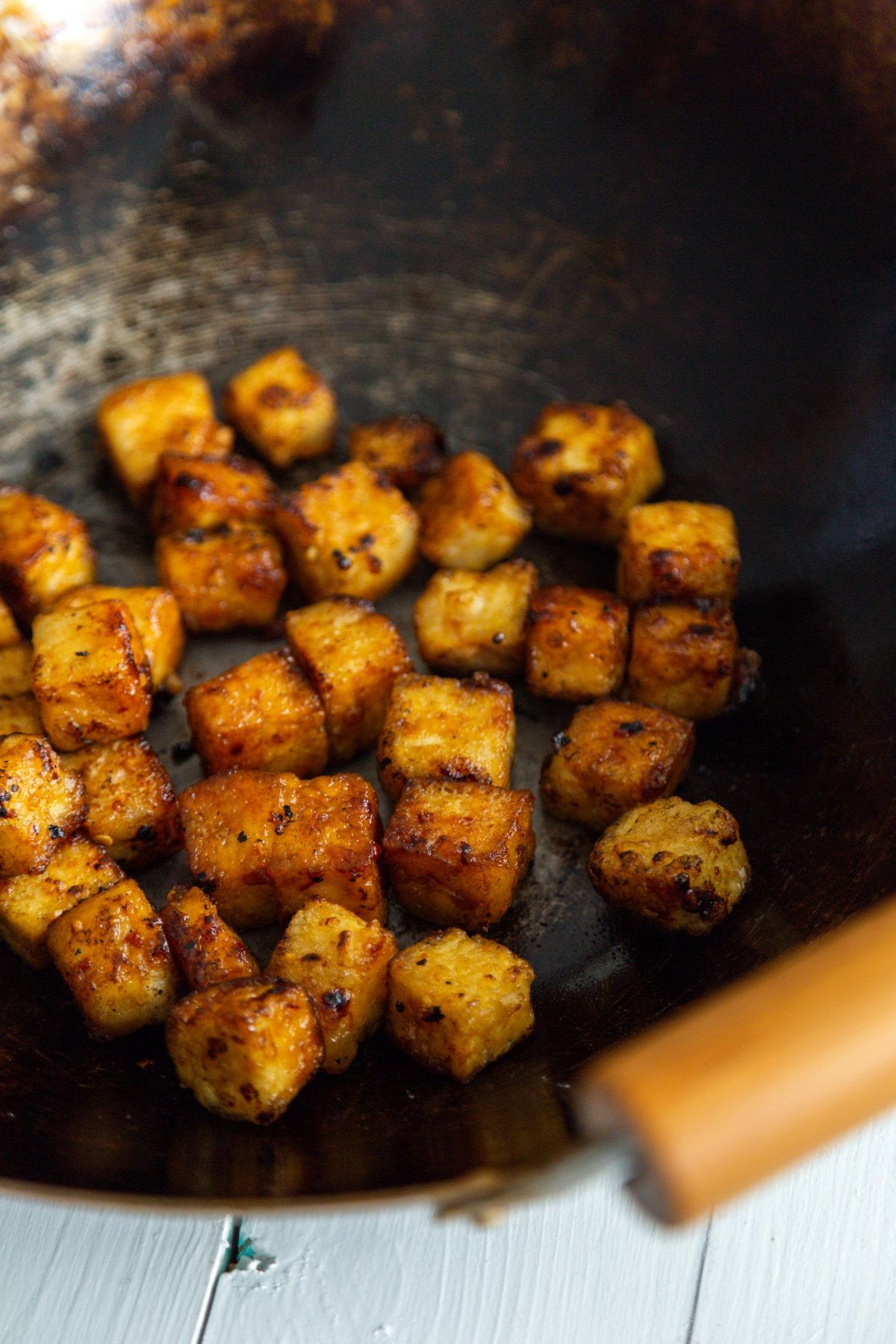 A close up picture of cubed fried tofu in a wok with wooden handles.
