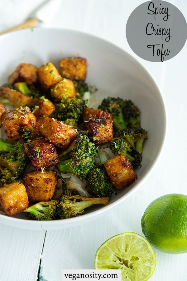 A Pinterest pin for spicy and crispy tofu with a picture of a white bowl with the tofu, broccoli, and rice and 2 halves of a lime next to the bowl.