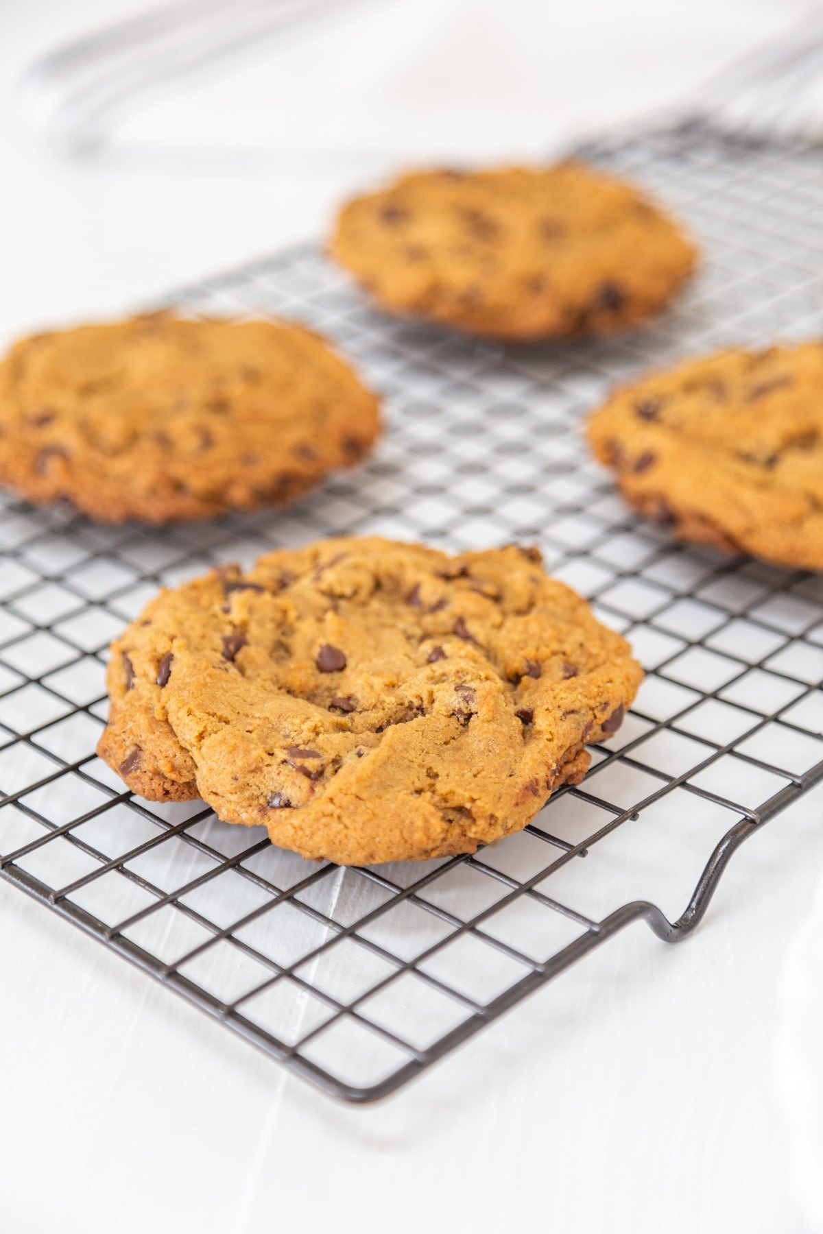 4 chocolate chip cookies on a wire cooling rack.