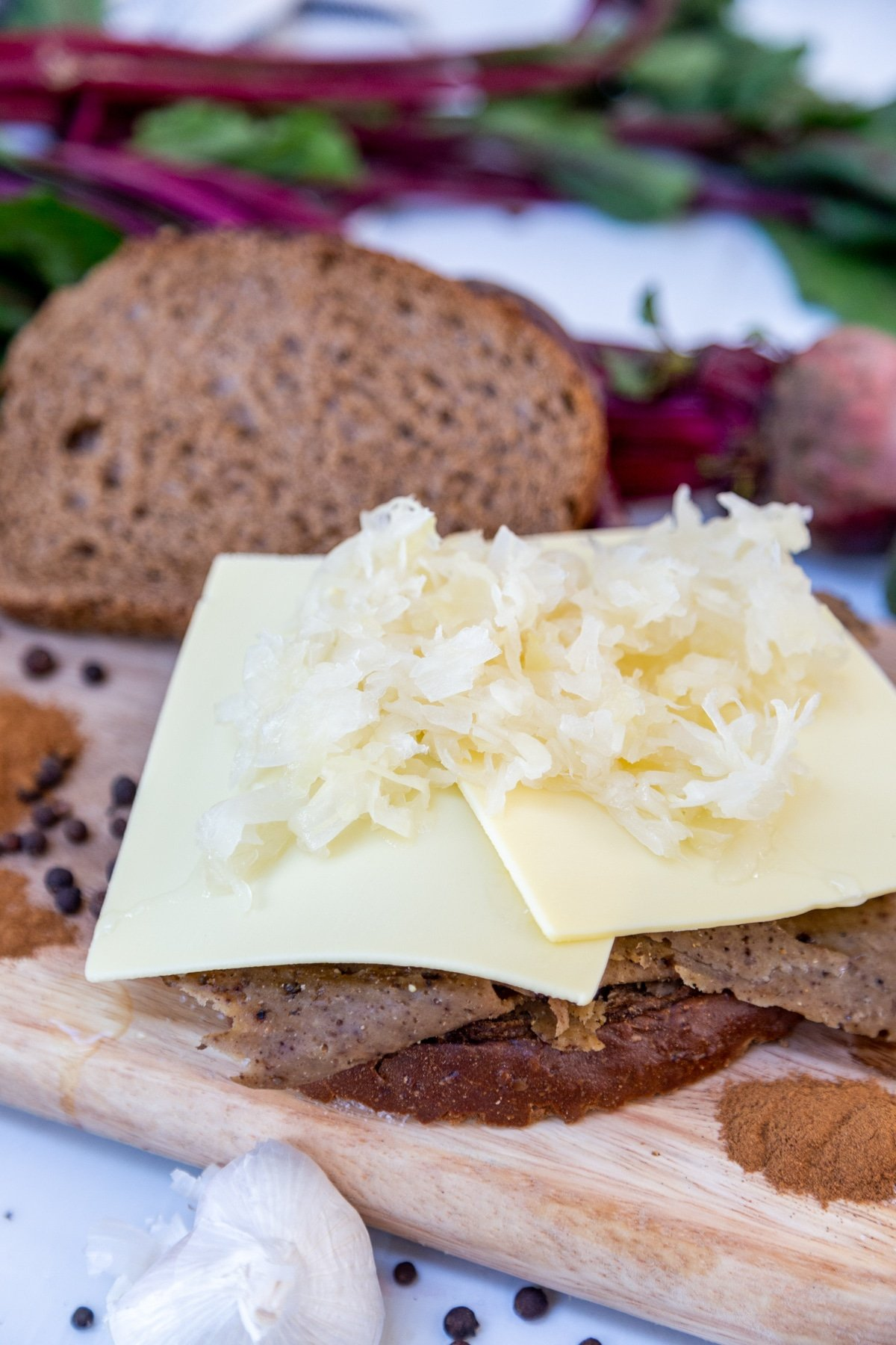 A slice of bread with corned beef, cheese, and sauerkraut.