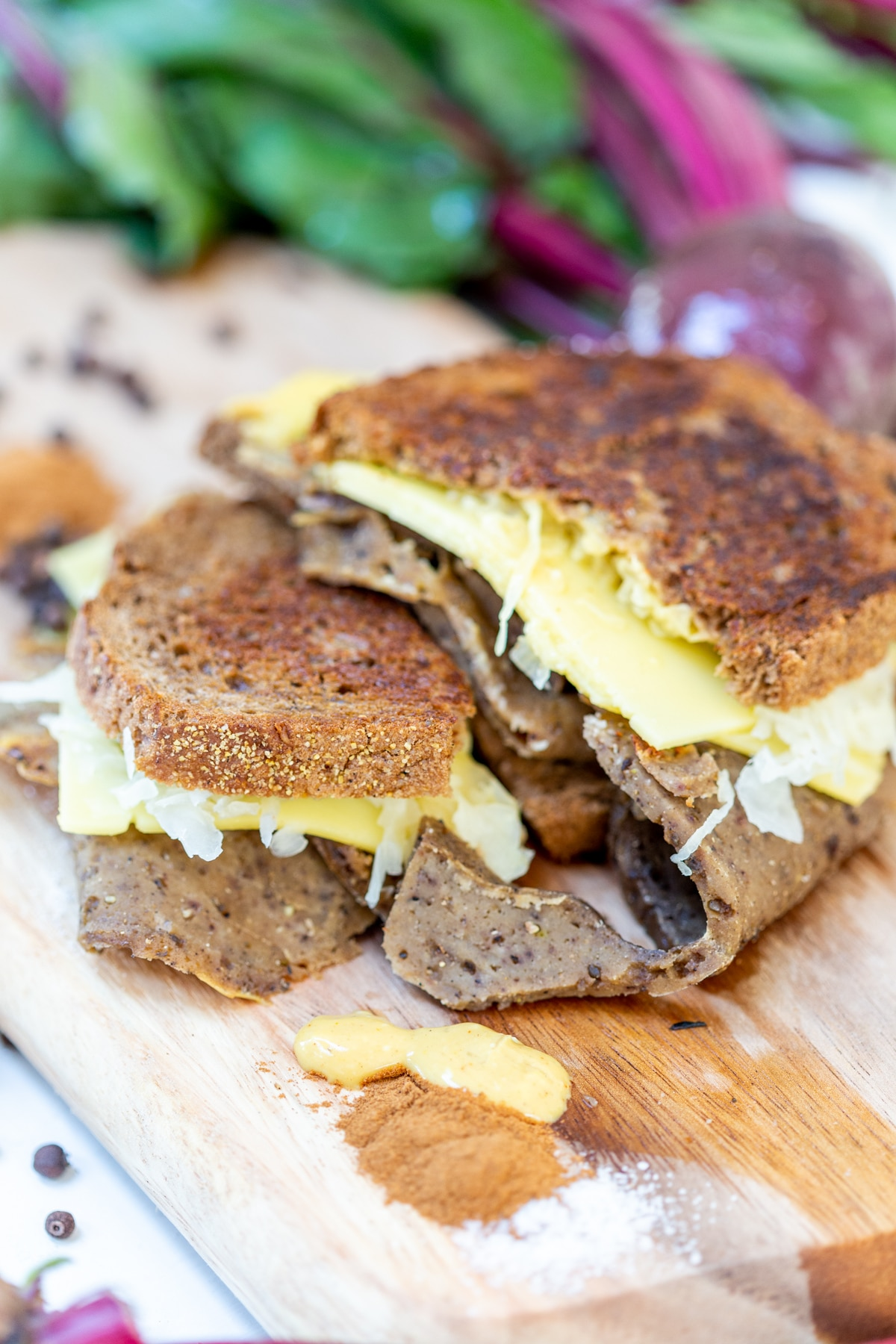 A Reuben sandwich on a wooden board with corned beef and sauerkraut falling out of the sides.