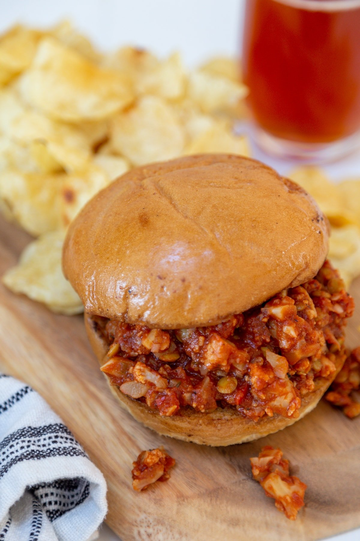 A sloppy Joe sandwich on a wooden board with potato chips and a glass of beer in the background.