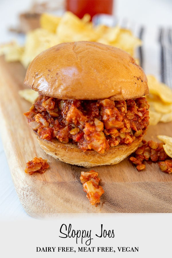 A Pinterest pin for vegan sloppy Joes with a picture of a sloppy Joe sandwich on a wooden board wit potato chips.