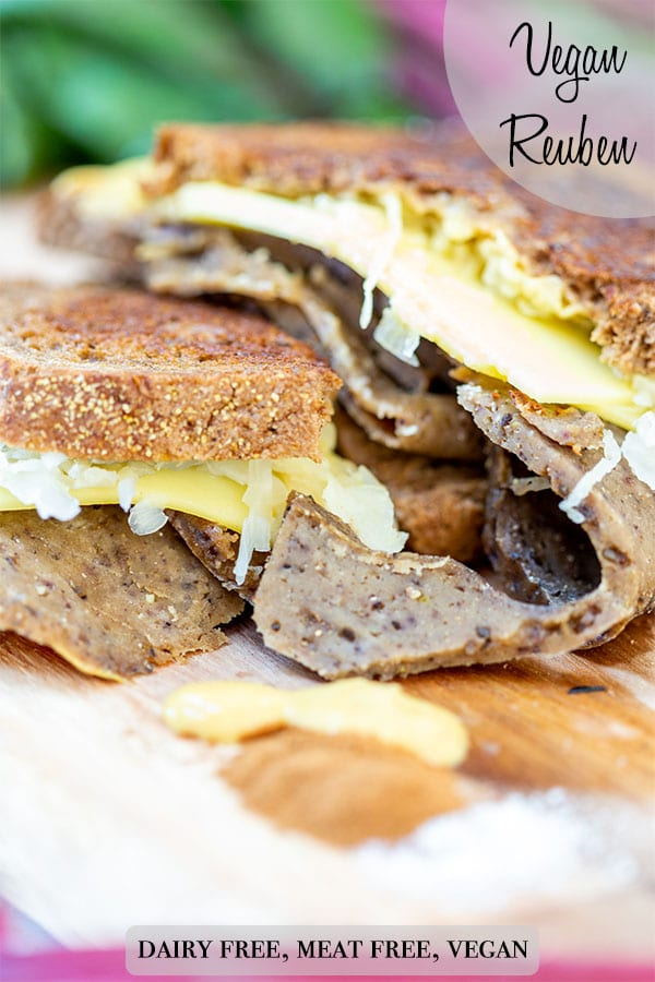 A Pinterest pin for a vegan Reuben sandwich with a picture of the Reuben cut in half on a wooden board.