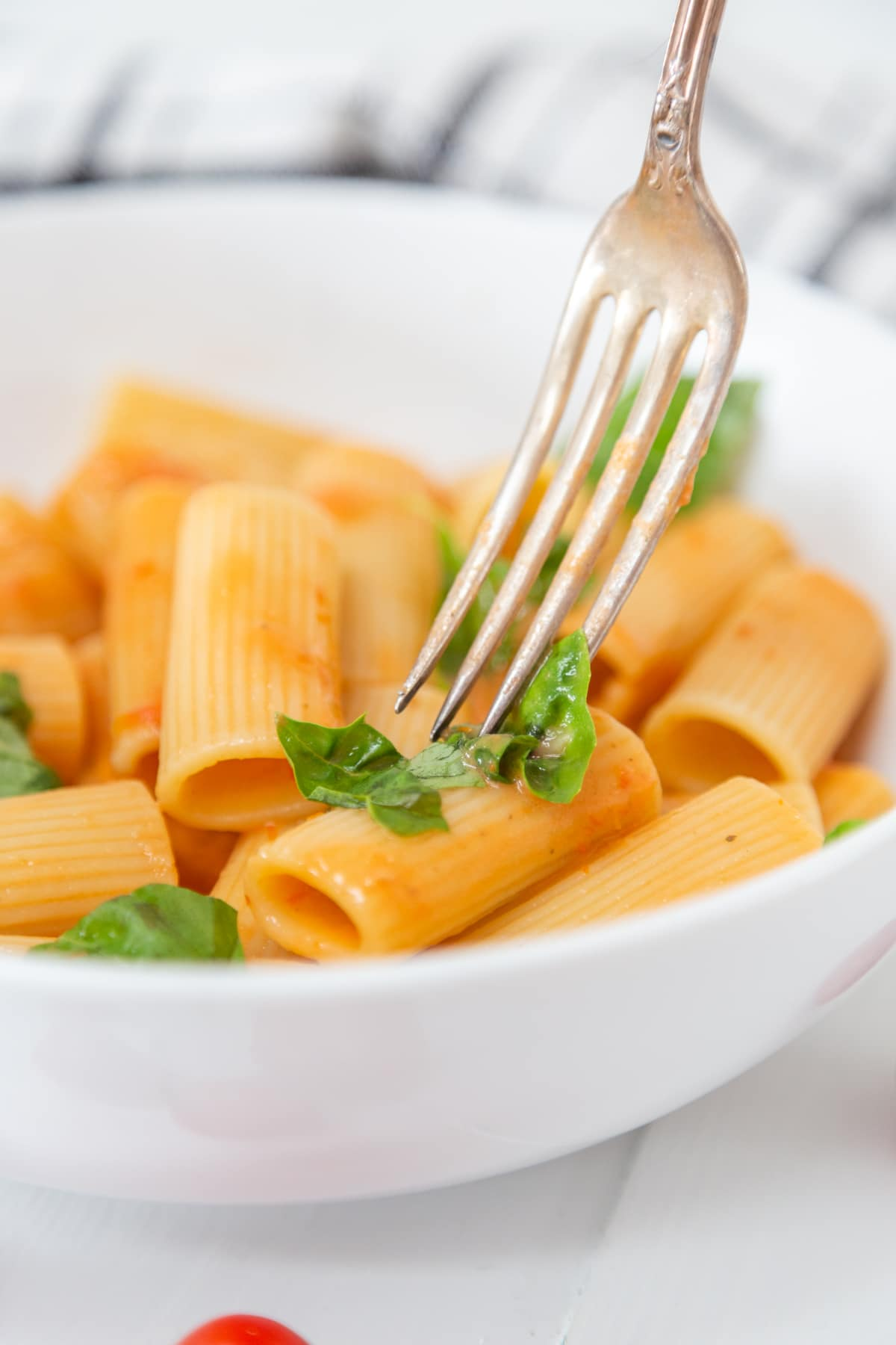 A silver fork piercing a piece of rigatoni with a creamy tomato sauce.