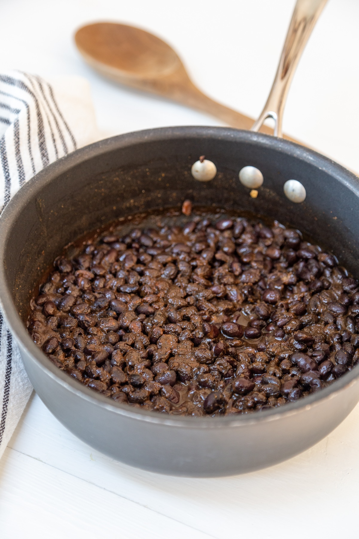 A pot of black beans with a wooden spoon and a black and white striped towel in the background.