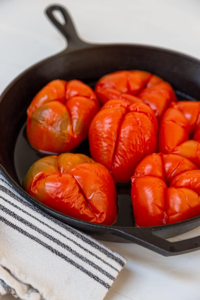 6 roasted red bell peppers in a cast iron skillet.