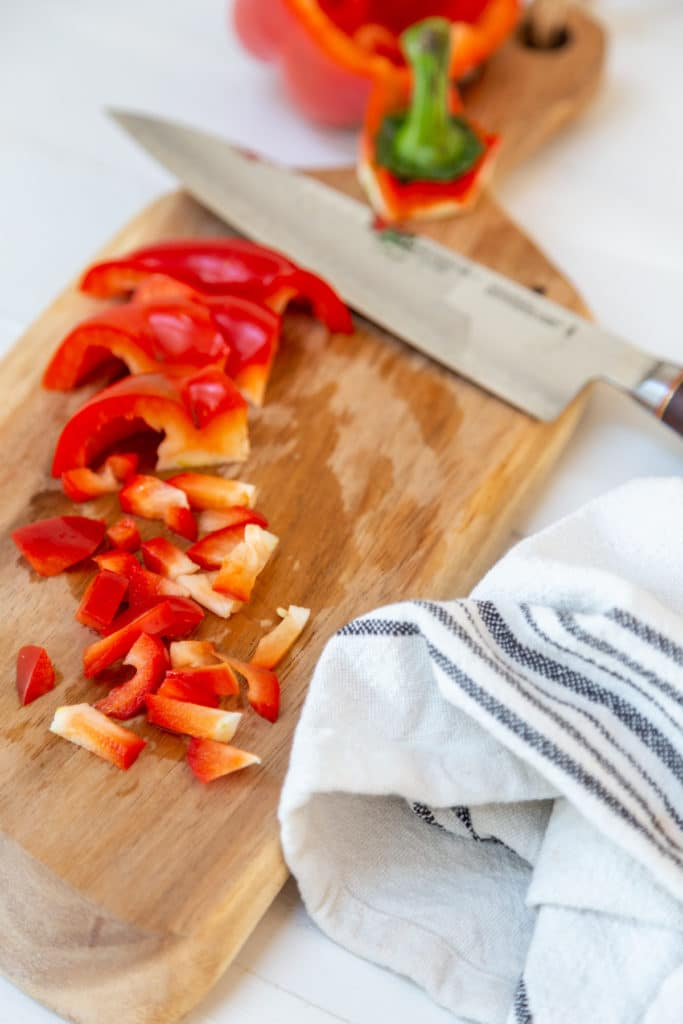 Diced red bell pepper on a wood cutting board with a chef's knife.