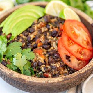 A wooden bowl with black beans, rice, and vegetables, topped with sliced avocados, tomato, and fresh cilantro.