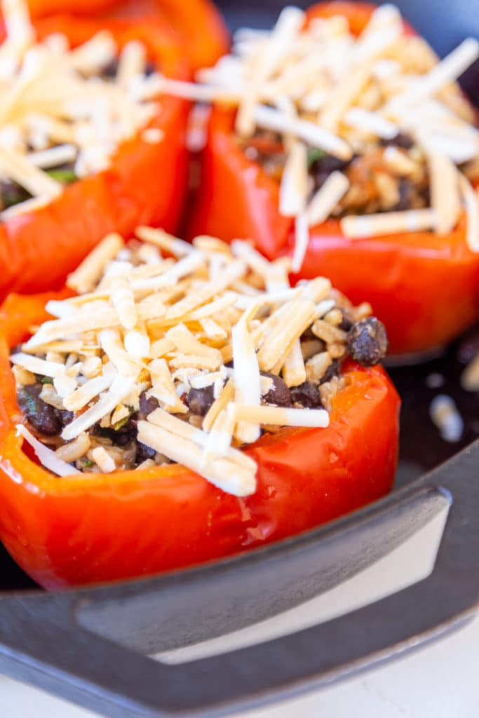 red bell peppers stuffed with beans and rice and topped with shredded cheese.