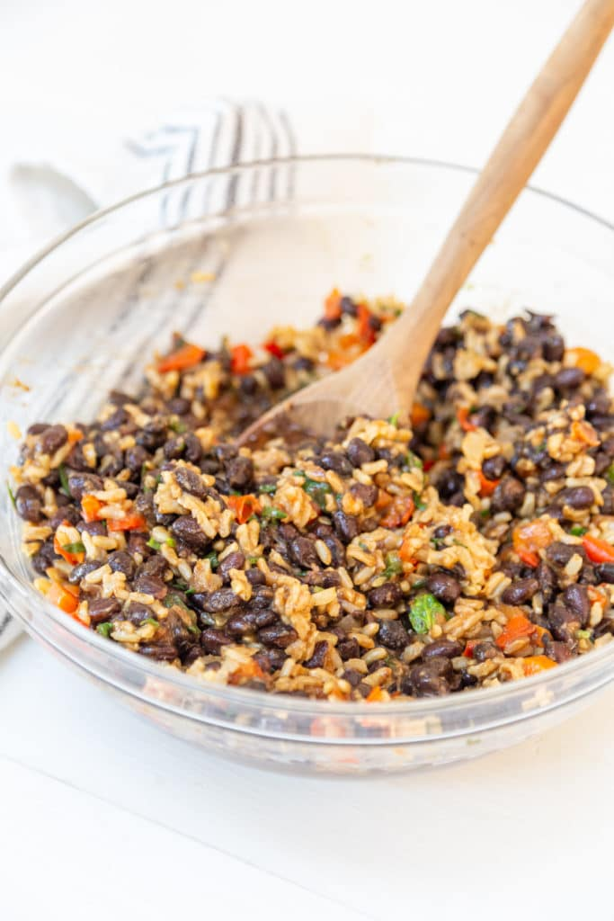 A clear glass bowl with a wooden spoon stirring black beans, rice and mixed vegetables.