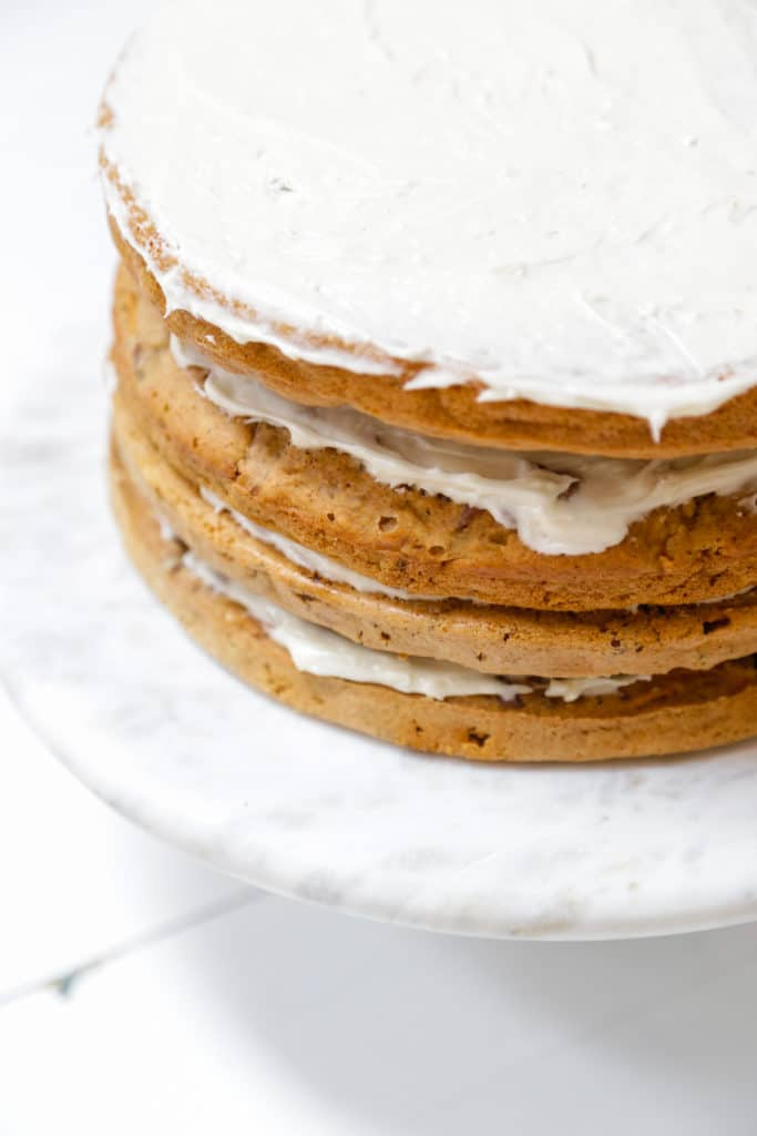4 layers of carrot cake with frosting between each layer and spread evenly on the top layer.