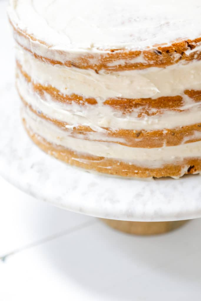 A 4 tiered carrot cake with cream cheese frosting.