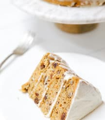 A slice of carrot cake with cream cheese frosting on a white plate with the whole cake in the background.