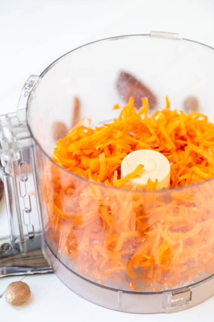 A food processor with shredded carrots.