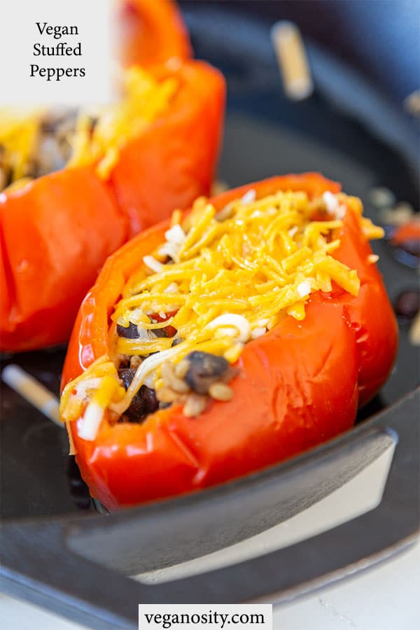 A Pinterest pin for vegan stuffed peppers with 2 peppers in a black pan.