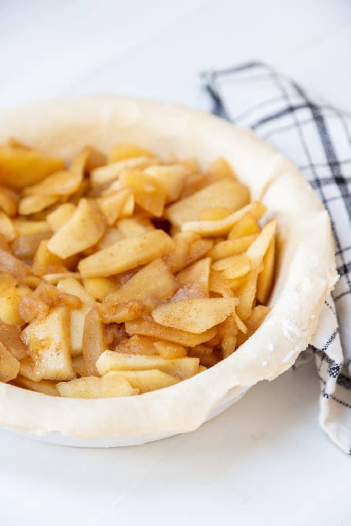A pie crust in a pie pan filled with cooked apples.