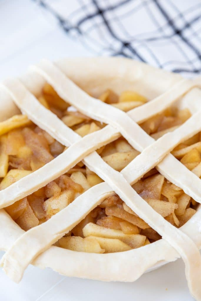 An apple pie with the beginnings of a lattice top.