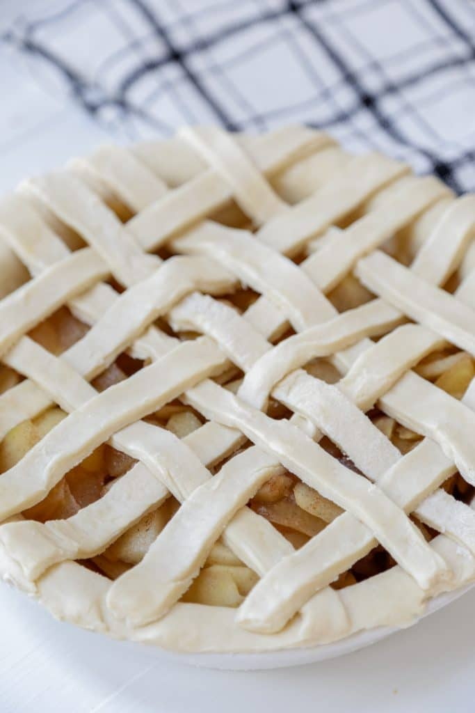 An unbaked apple pie with a lattice top.