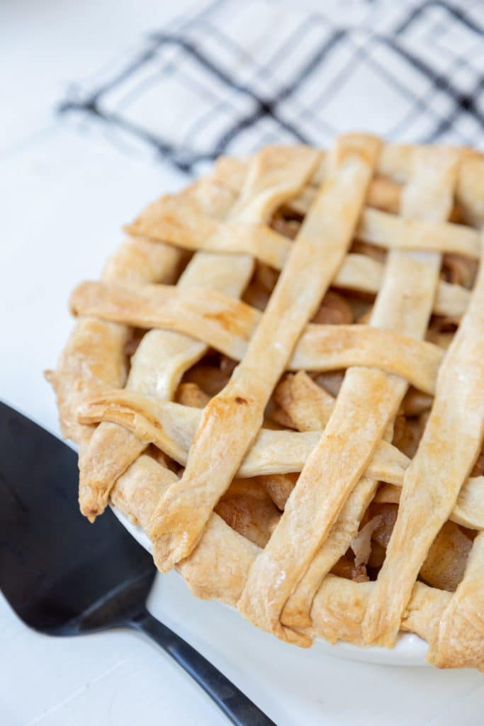 An apple pie with a lattice top and a black pie spatula next to the pie.