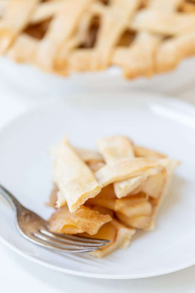 A slice of apple pie with a silver spoon on a white plate and a lattice top apple pie in the background.