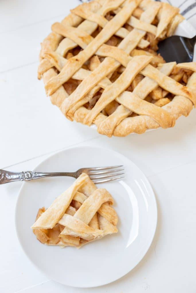 An apple pie with a lattice top and a slice of the pie on a white plate.
