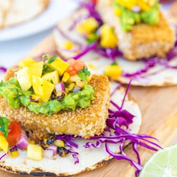 Breaded tofu tacos with mango salsa on a wooden board.