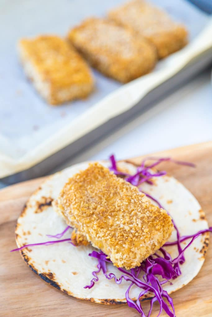 A tortilla with shredded purple cabbage and a breaded fried piece of tofu.