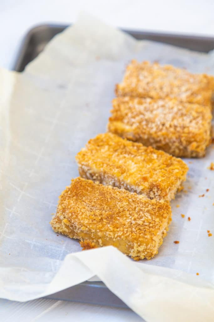 Deep fried pieces of tofu on a parchment lined baking sheet.