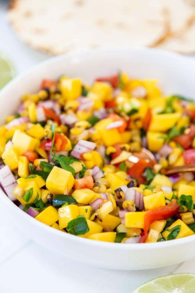 A white bowl with mango salsa.