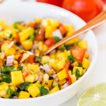 A white bowl with mango salsa and a gold spoon in the bowl.