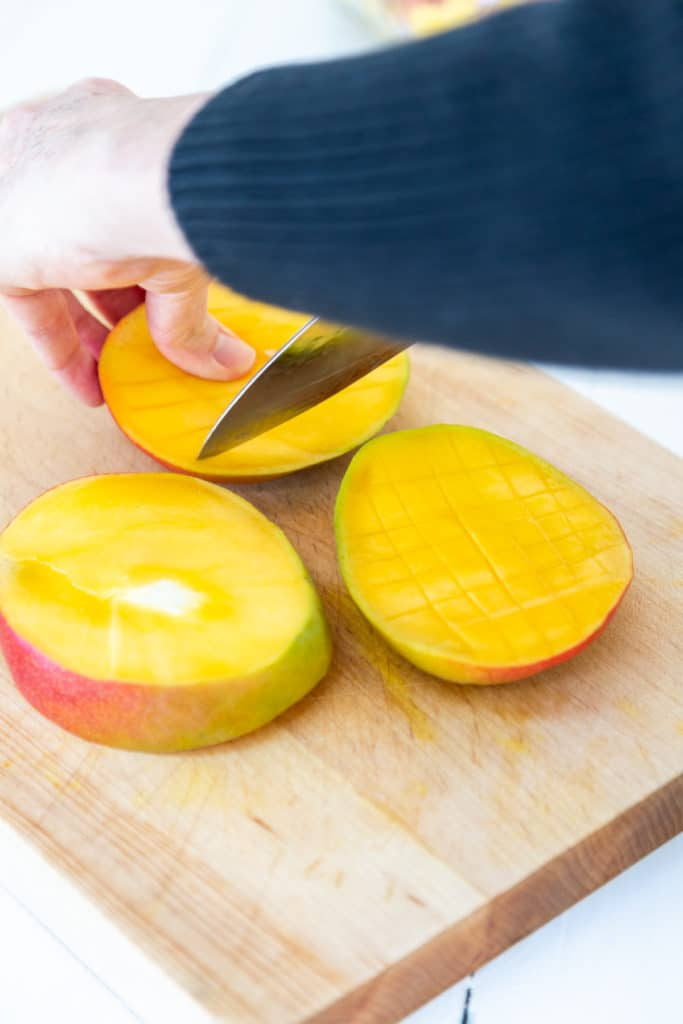 A woman dicing a mango with a chef's knife.