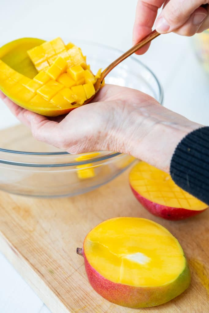 A hand holding a gold spoon that's scooping out cubed mango into a bowl.