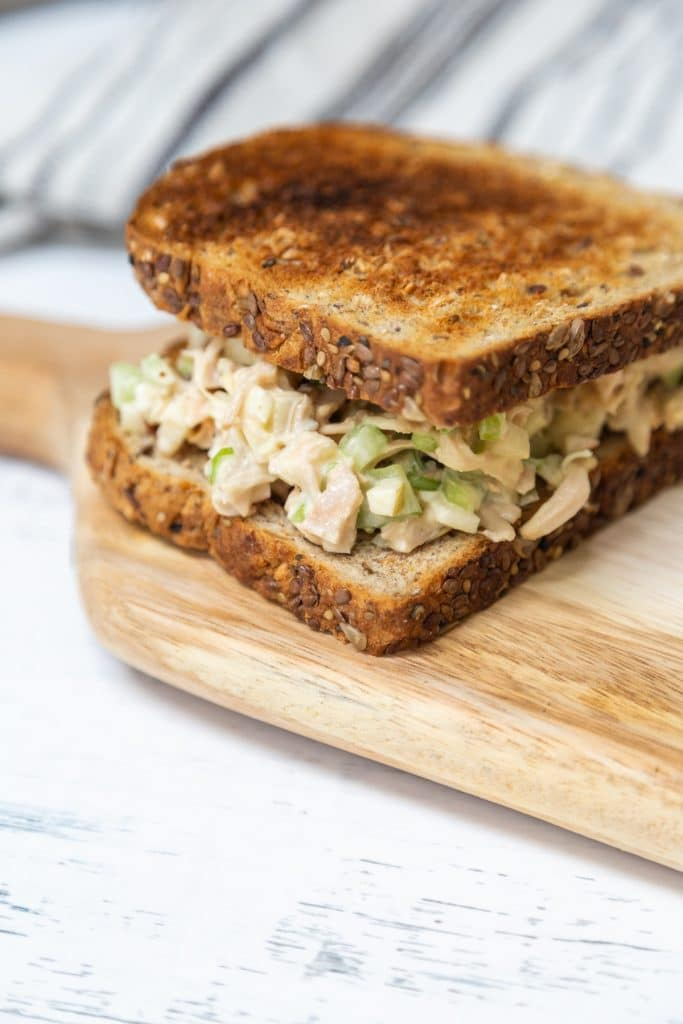 A chicken salad sandwich on toast that's sitting on a wooden board.
