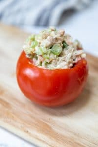 A red tomato stuffed with chicken salad on a wooden board.
