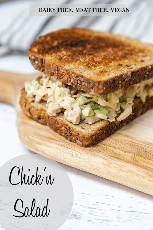 A Pinterest pin for vegan chicken salad with a chicken salad sandwich on toast sitting on a wooden board.