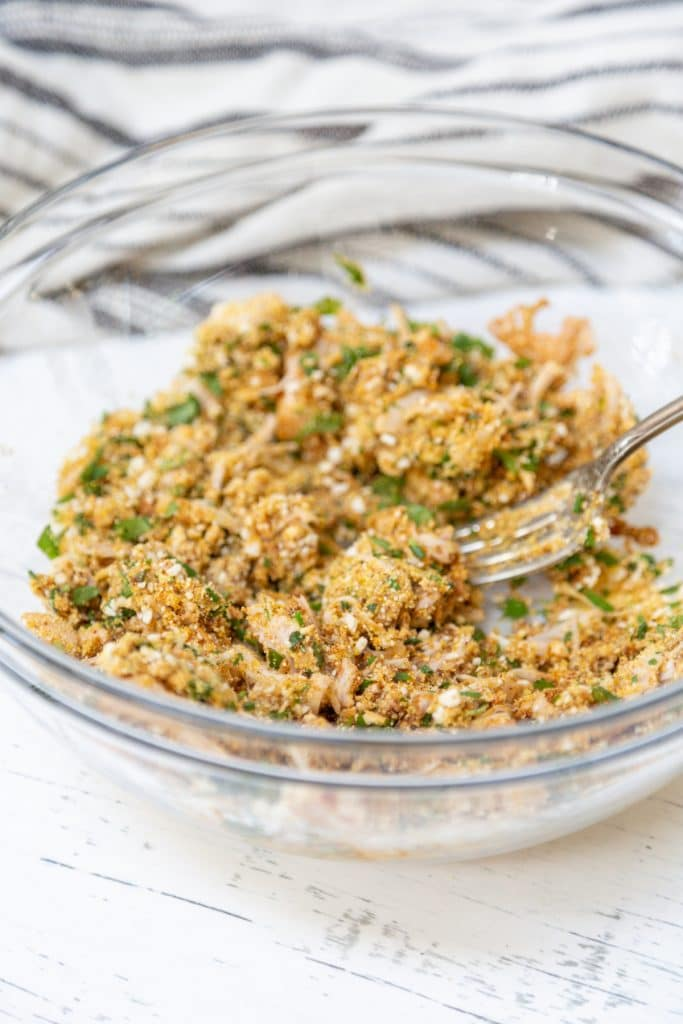 A clear glass bowl with uncooked crab cake mixture.