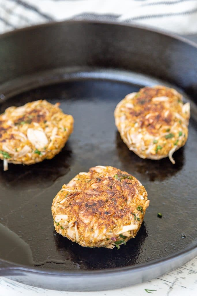 3 fried crab cakes in a cast iron pan.