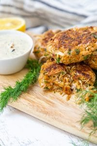 Crab cakes piled on a wooden board with a bowl of tartar sauce and dill.